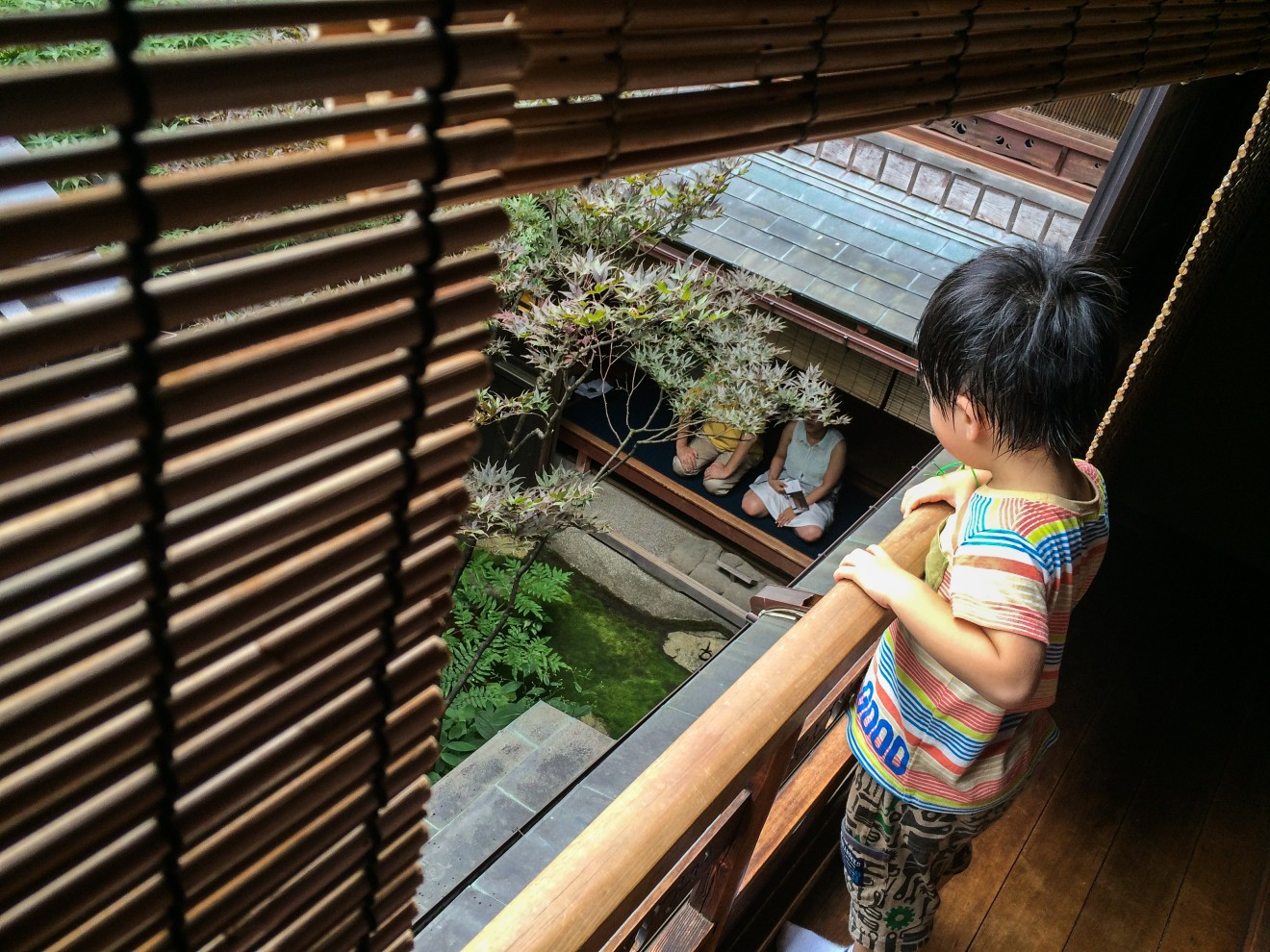 Child watches visitors meditate at the Shima Geisha House, Kanaz