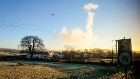 Through the train window, the Burneside paper mill makes cloud for the morning sky