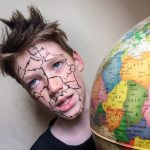 Boy with map on his face in front of globe